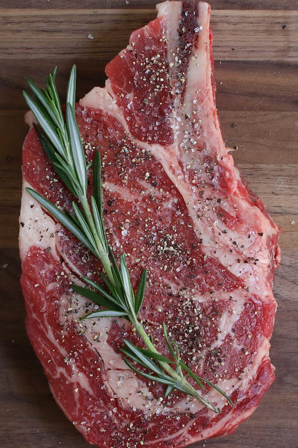 Bone-in rib eye steak before cooking seasoned with salt and pepper with a sprig of rosemary