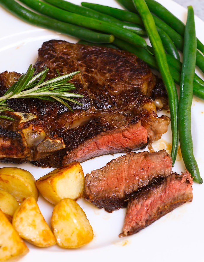 Closeup of sliced rib eye steak that has been perfectly cooked to medium rare doneness and served with green beans, sauteed potatoes and a sprig of fresh rosemaryon the side