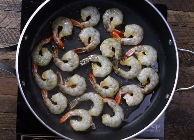 This photo shows sautéing large size shrimp in a skillet with oil, and the color starting to turn pink on the edges