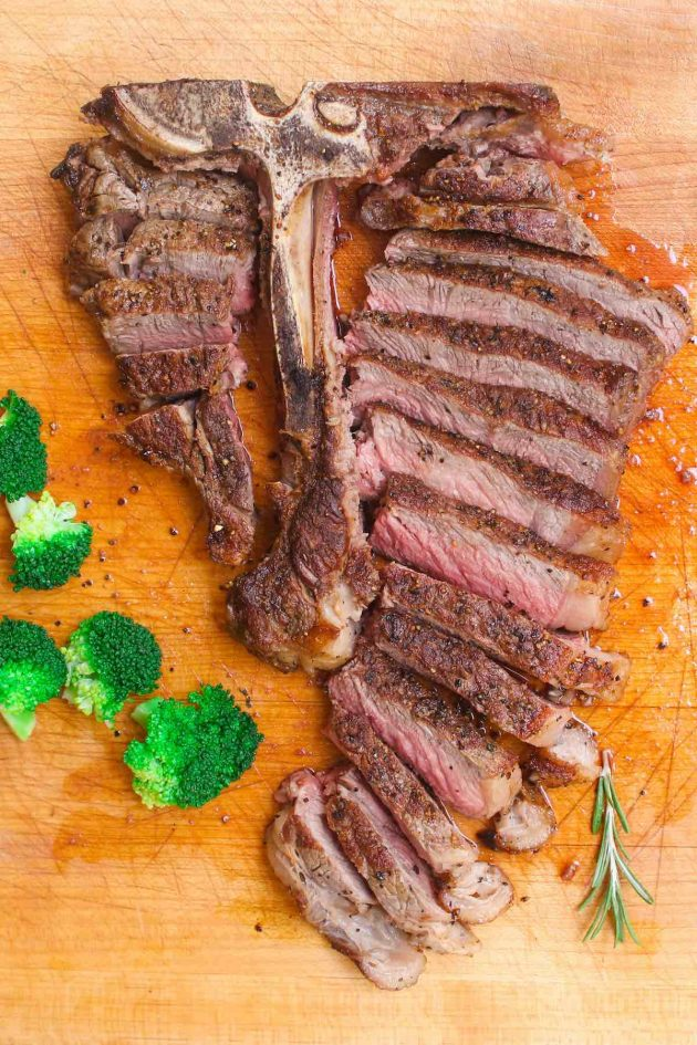 T-bone steak on a cutting board after being prepared for serving by cutting the meat away from the bone and slicing into thin pieces