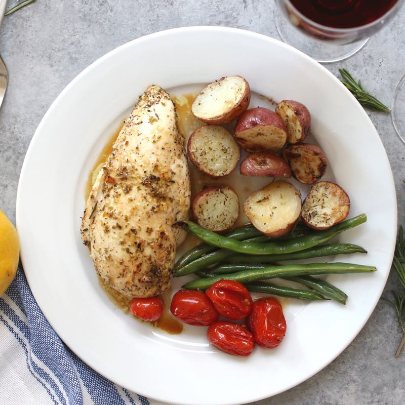 Sheet pan chicken and vegetables served on a plate with pan juices and a glass of red wine. Delicious!