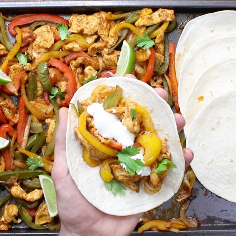 Baked Chicken Fajitas - this photo shows a flour tortilla loaded with chicken fajita filling and garnished with sour cream and cilantro