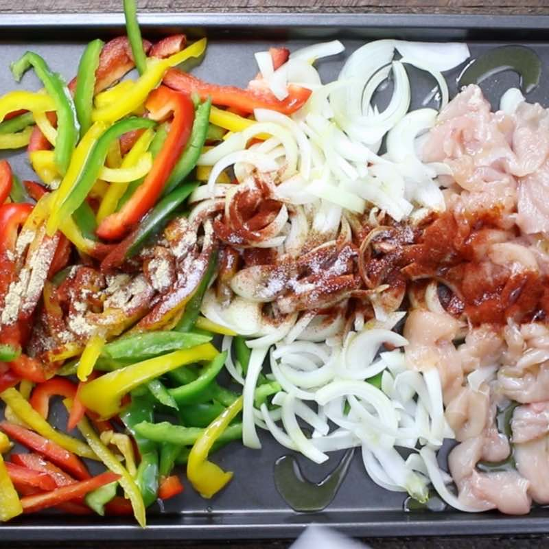 This is a photo of the raw ingredients for chicken fajitas on a sheet pan before being mixed together: chicken, onions, bell peppers, seasonings and vegetable oil