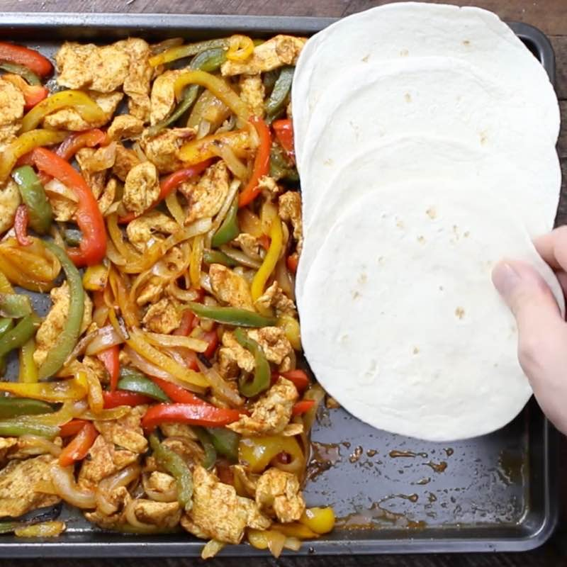 Baked Chicken Fajitas - this photo shows a sheet pan with cooked chicken fajita ingredients with hot flour tortillas on the side