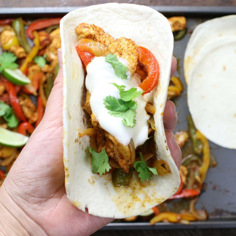 Here is a closeup photo of a chicken fajita freshly assembled off a sheet pan and ready to eat