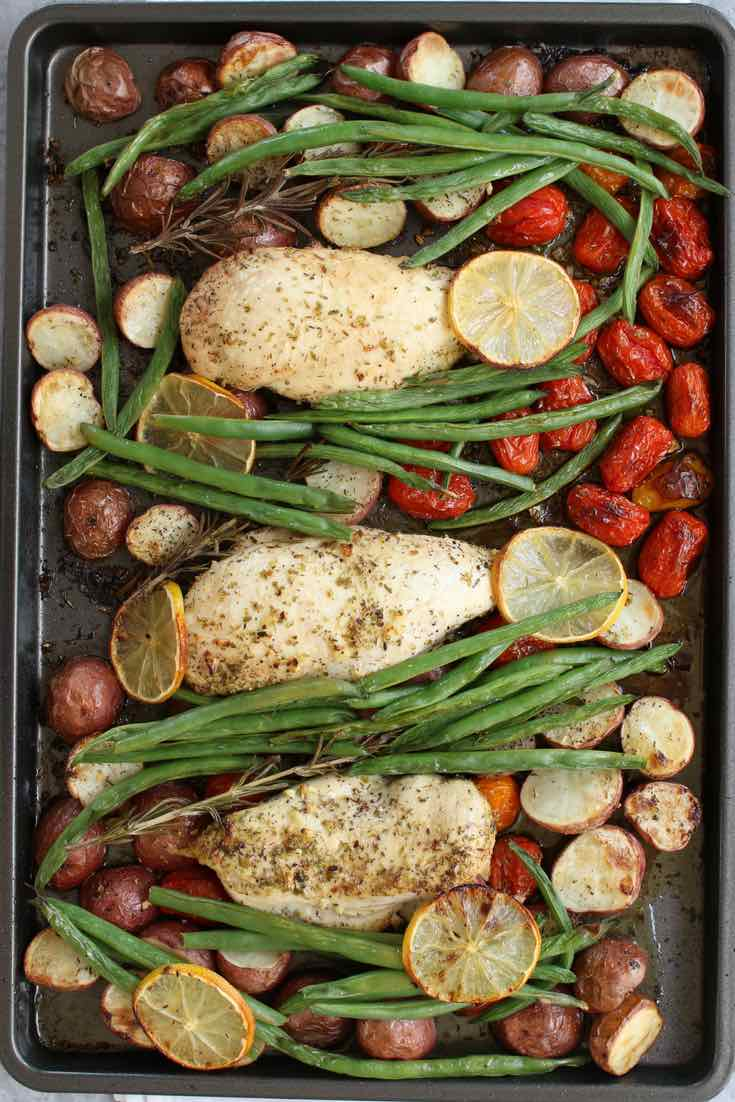 This photo shows the beautiful roasted chicken breasts, potatoes, cherry tomatoes and green beans on the sheet pan coming out of the oven, ready to be served