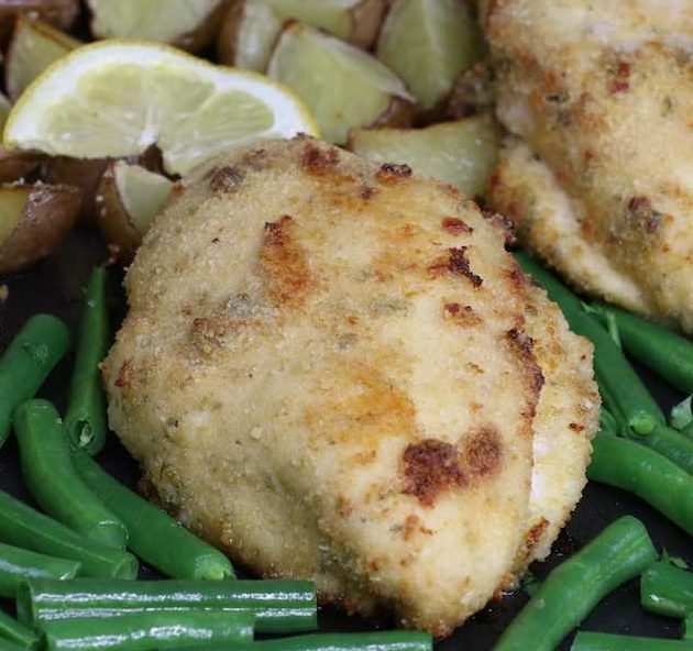 Breaded chicken with green beans and potatoes on a baking sheet