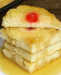 Stack of pineapple upside down pancakes on a serving plate with maple syrup drizzled on top