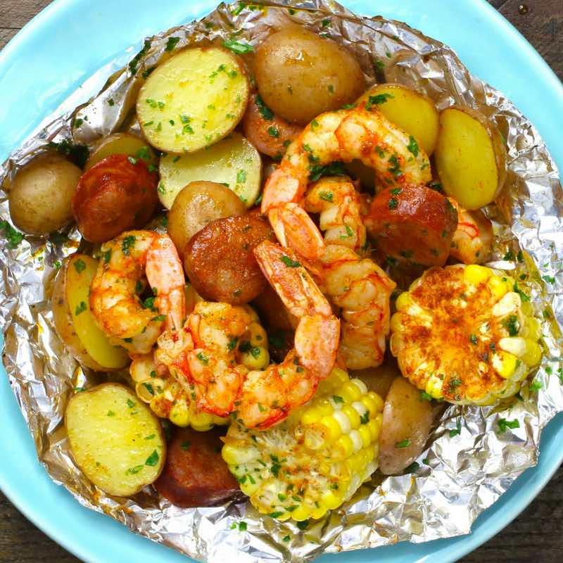 Shrimp Boil Packets - this is a photo of a shrimp boil in a foil packet opened up on a serving plate ready to be eaten