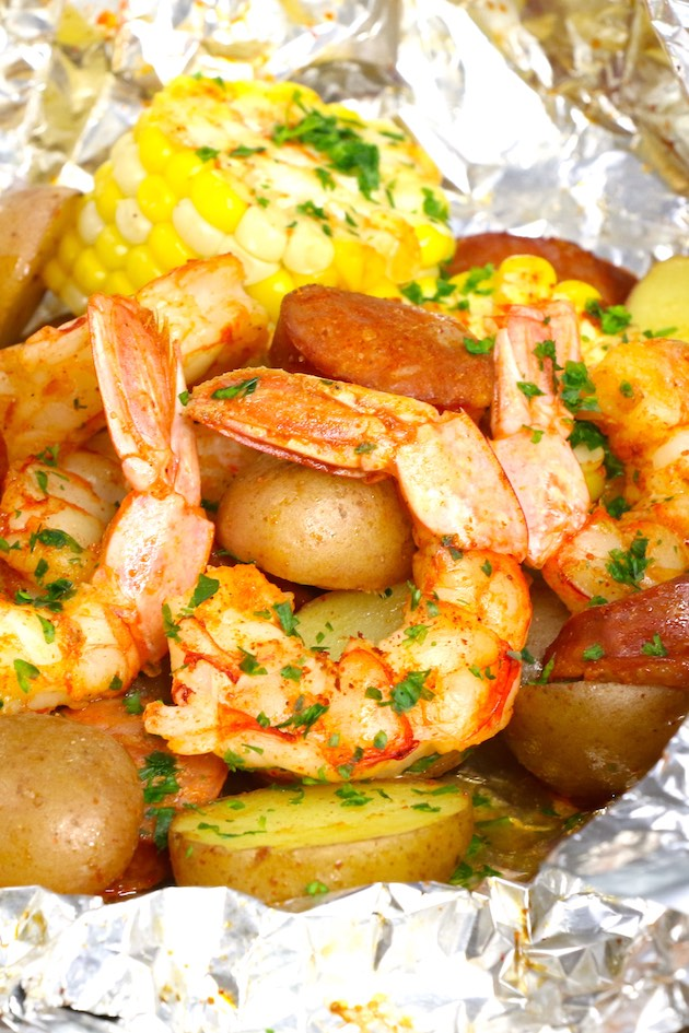 This shrimp boil in foil is a delicious combination of jumbo shrimp, baby potatoes, corn and sausage with Old Bay seasoning, grilled and garnished with lemon juice and parsley for a delicious Cajun meal