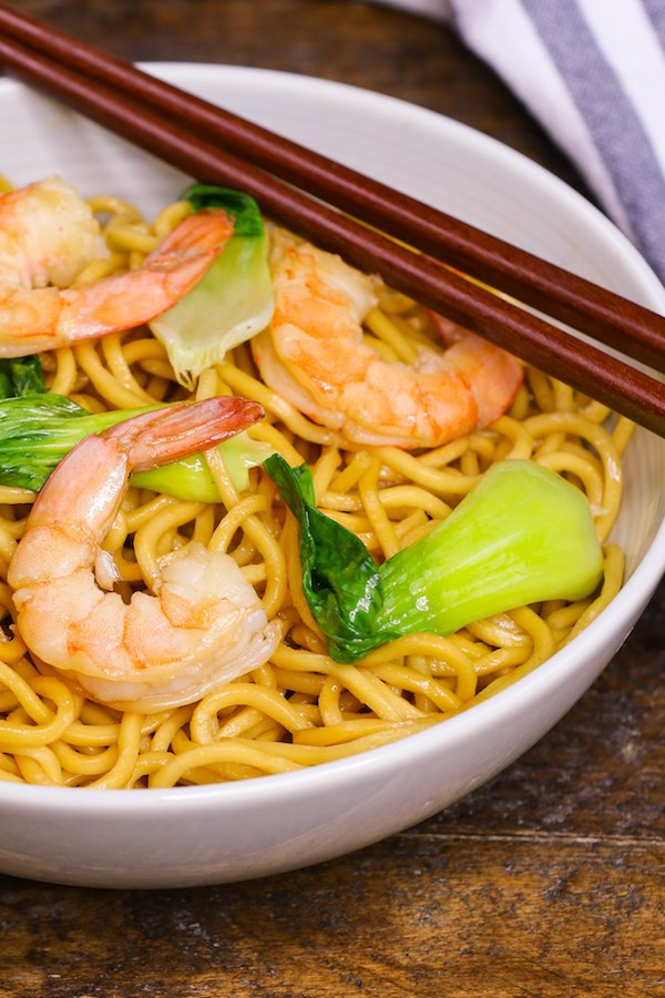 A bowl of chow mein noodles containing shrimp and bok choy, with chopsticks on the side