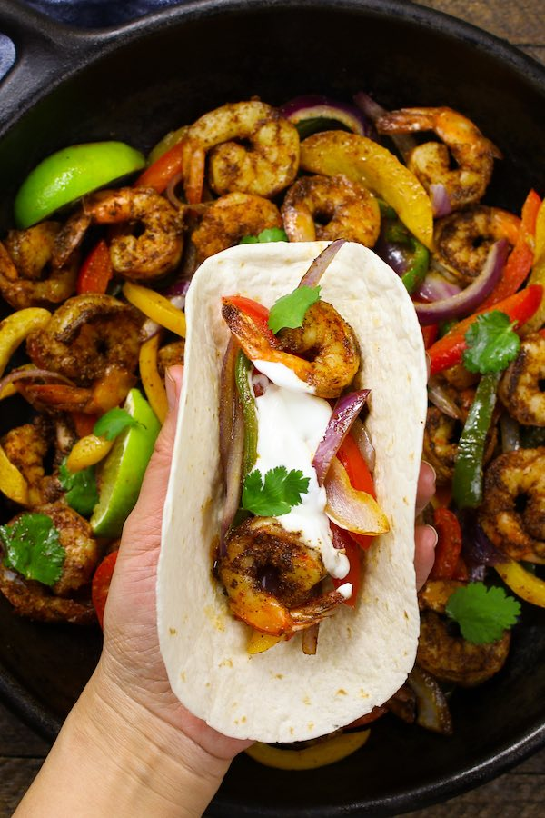 Shrimp Fajitas topped with sour cream, cilantro and served on tortilla