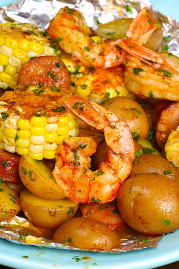 Closeup of Shrimp Foil Packets on a serving plate showing juicy jumbo shrimp, potatoes, sausage, potatoes and corn with Cajun seasoning, fresh lemon juice and minced parsley. The perfect summertime foil packet meal!