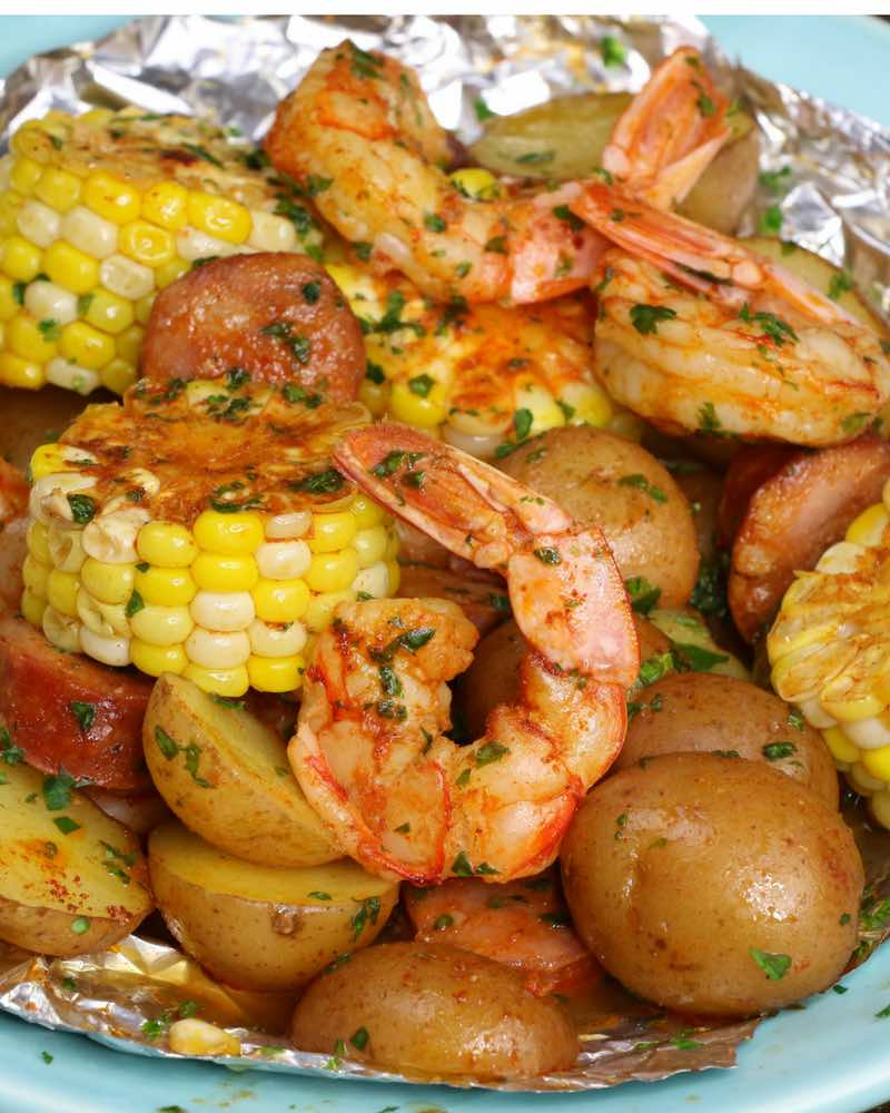 This is a photo of a shrimp boil packet with corn, potatoes and sausage on plate after being cooked