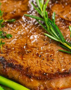 Closeup of pan seared sirloin steak that has been nicely browned with fresh rosemary and thyme as garnish