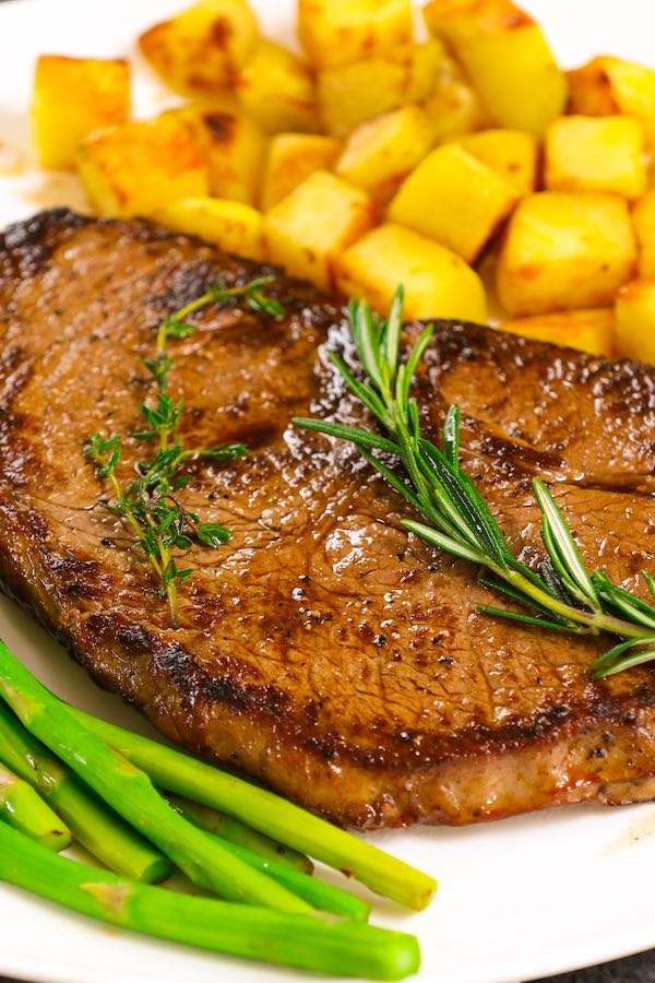 Delicious sirloin steak served with green asparagus and potatoes with fresh thyme and rosemary for garnish