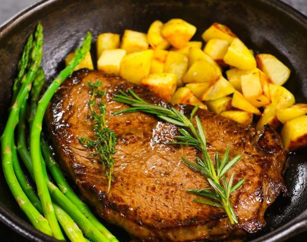 Sirloin steak cooked to perfection in a cast iron pan with green asparagus and new potatoes with fresh thyme and rosemary