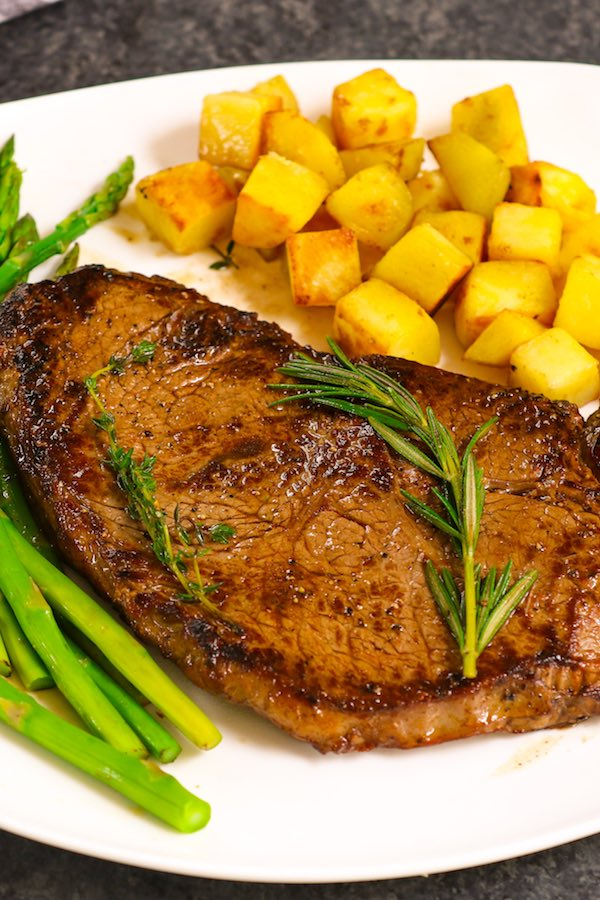 Cooked Sirloin Steak with garlic butter on a serving plate with sauteed potatoes, asparagus, fresh thyme and rosemary for an easy dinner idea