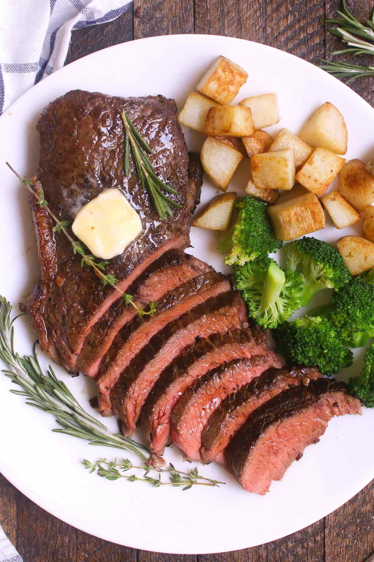 Overhead view of a sirloin steak dinner consisting of sliced top sirloin garnished with fresh rosemary, thyme and a pat of butter, served with sautéed potatoes and broccoli