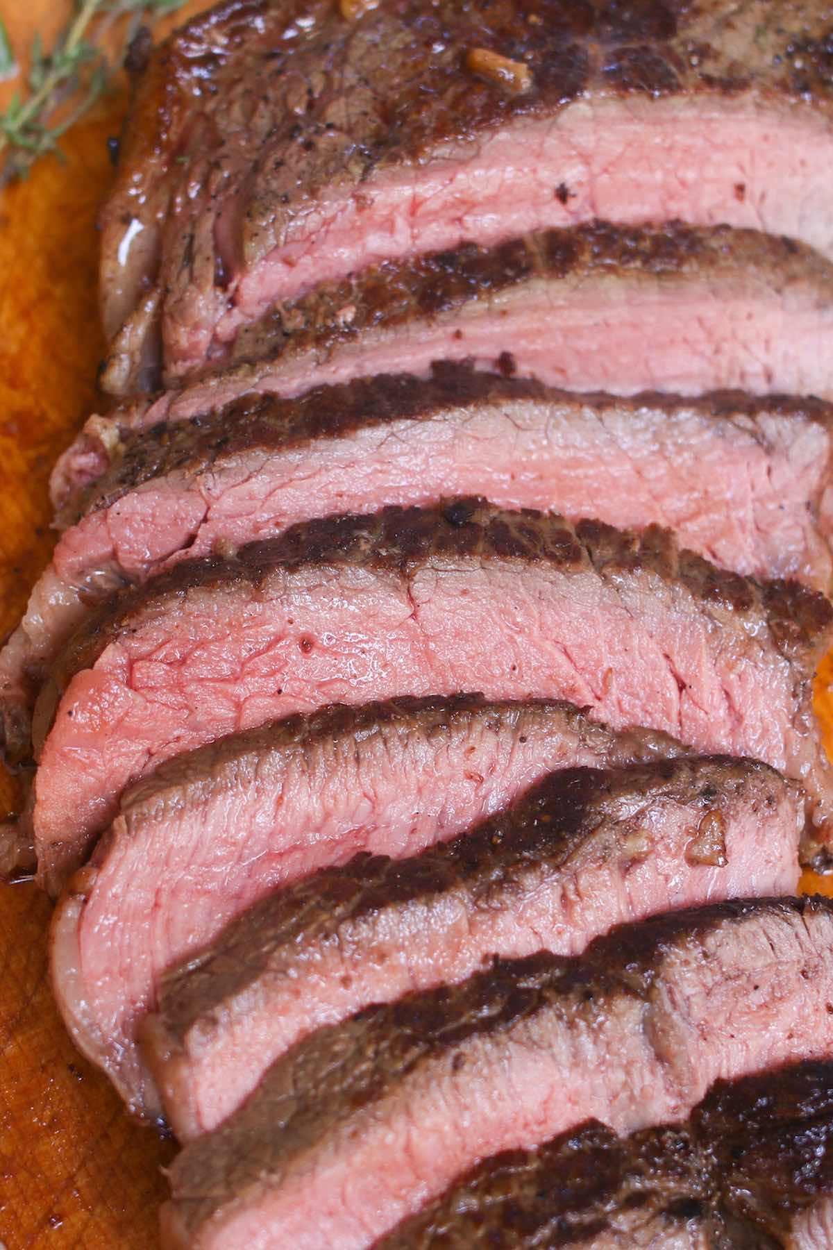 Closeup of pan seared sirloin steak cooked to medium doneness and sliced thinly