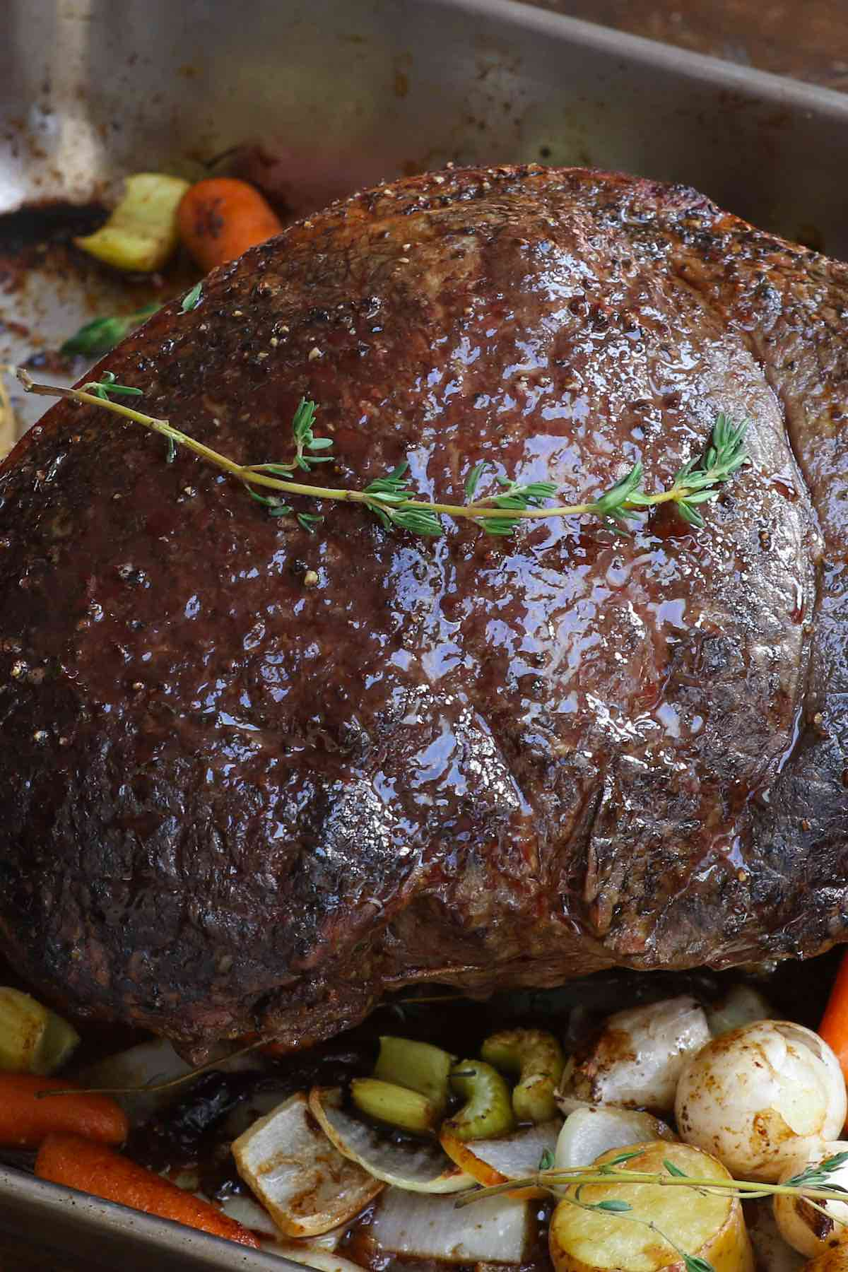 Sirloin roast in a roasting pan with vegetables