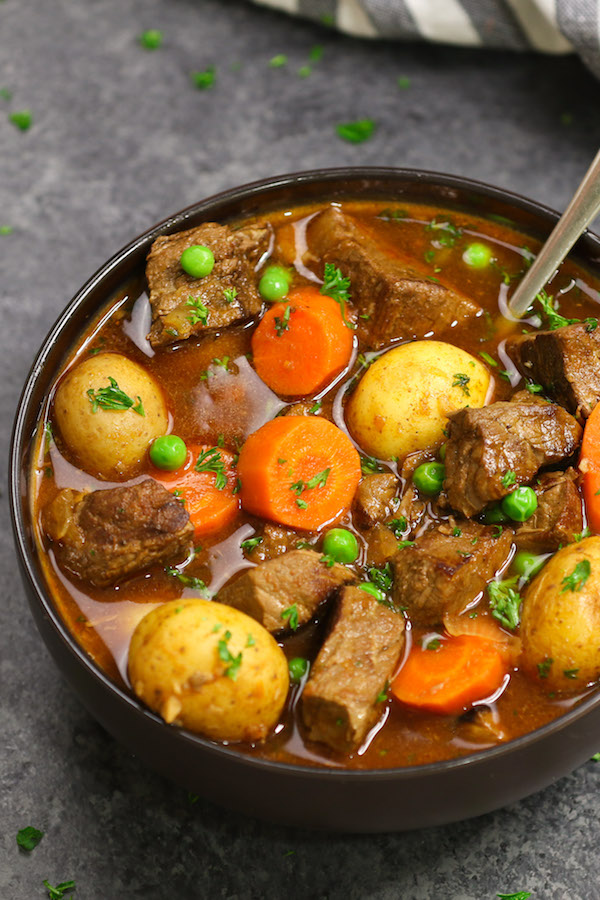 Bowl of slow cooker beef stew garnished with minced parsley on top