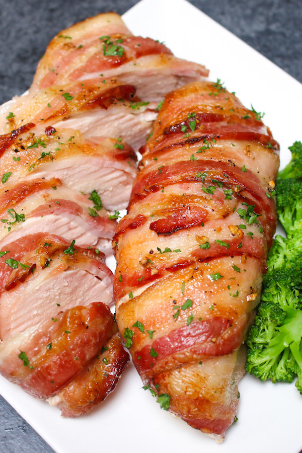 Slow Cooker Bacon Garlic Chicken Breast on a serving plate showing tender and juicy chicken breast wrapped with crispy bacon garnished with fresh parsley with broccoli on the side