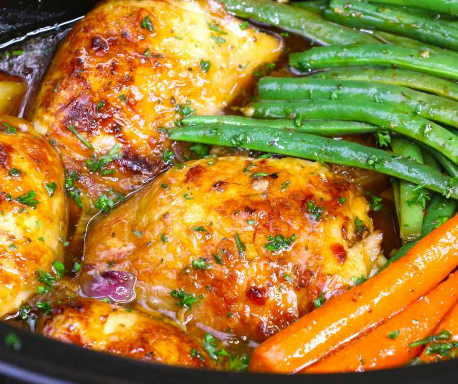 Closeup of slow cooker chicken thighs with carrots and green beans with a honey garlic sauce and minced fresh parsley, an easy weeknight dinner idea
