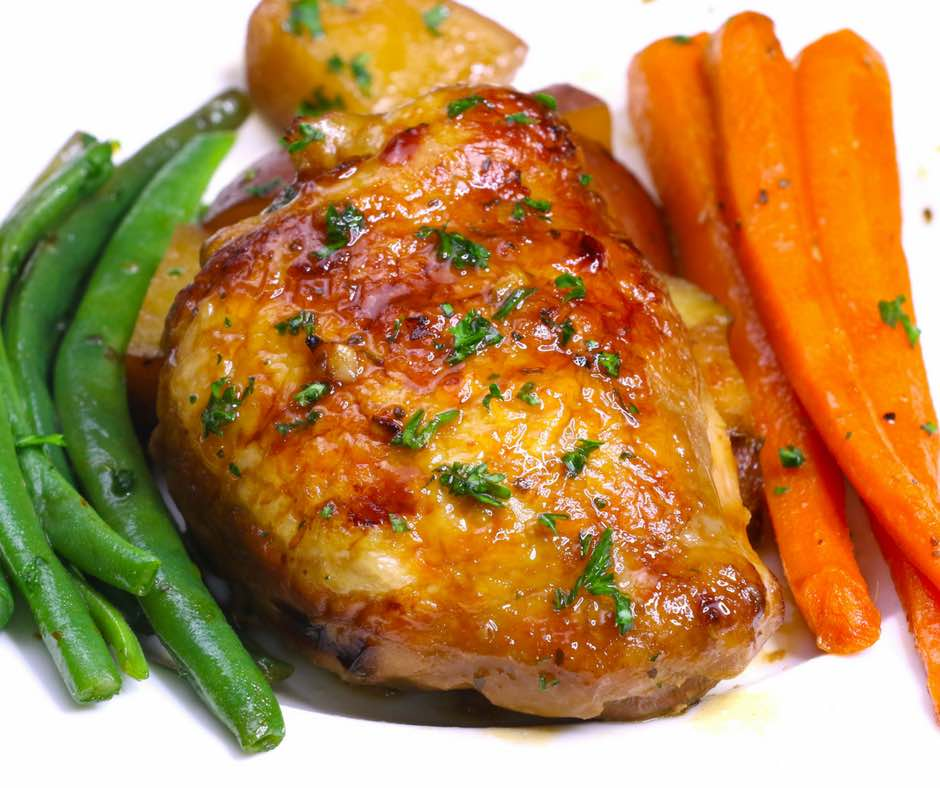 Crock Pot Honey Garlic Chicken on a serving plate with potatoes, carrots and green beans, showing off mouthwatering golden colors