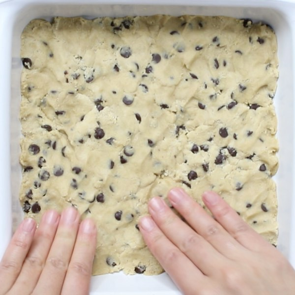 Slutty Brownies - cookie dough is the first layer in this dessert and this photo shows how to easily press it into a square pan with your fingertips to about a half inch thickness