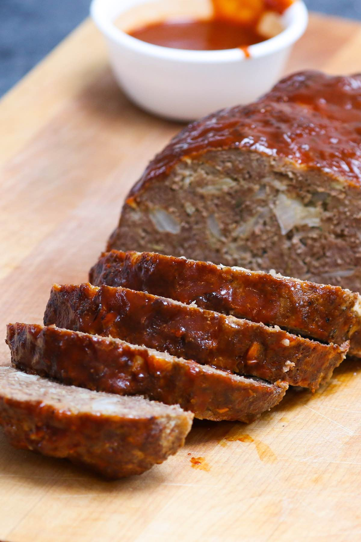 Sliced meatloaf fresh out of the smoker with BBQ sauce on the side