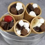 Easy S'mores Campfire Cones – An easy and fun summer treats recipe. All you need is only a few ingredients: ice cream cones, mini-marshmallows, banana, raspberry, mini peanut butter cups and chocolate bars. This recipe can be customized with your favorite candies or fruits. Campfire recipe. Quick and easy recipe. Video recipe. | Tipbuzz.com