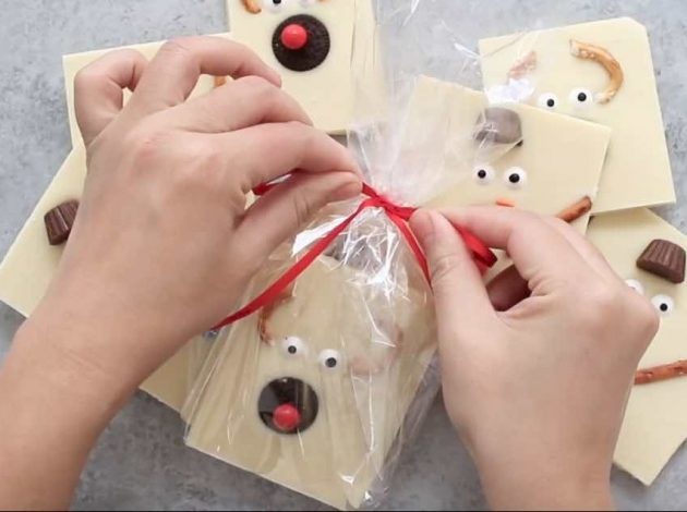 Wrapping up pieces of white chocolate bark into DIY holiday gifts for friends, family, teachers and neighbors