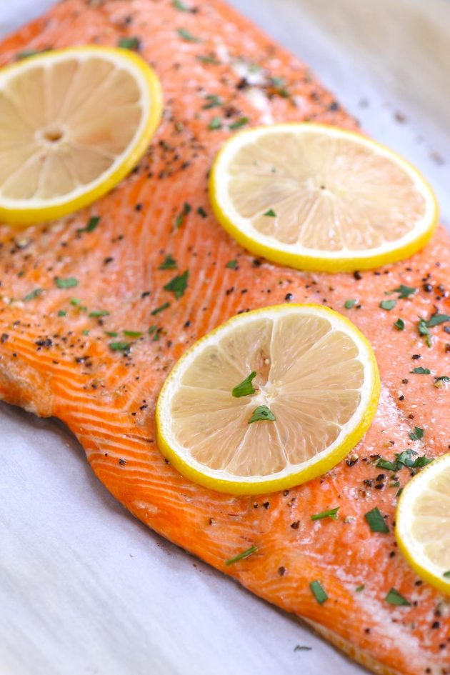 Delicious wild sockeye salmon baked to perfection with salt, pepper and lemon slices and garnished with minced fresh parsley