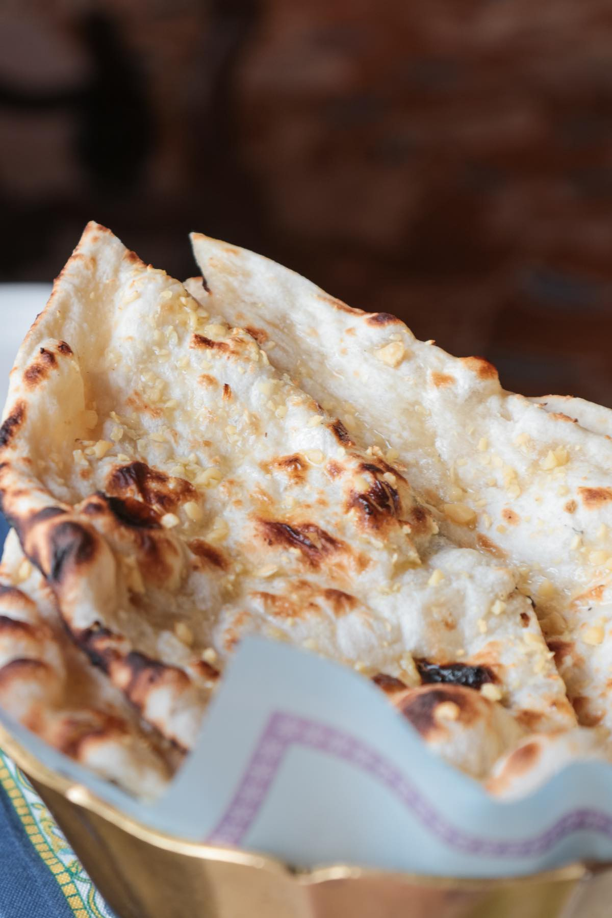 A basket of freshly made naan with golden minced garlic on top