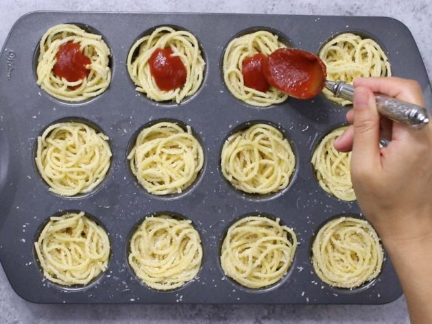Adding the sauce to the spaghetti in a muffin tin when making Spaghetti Meatball Cups