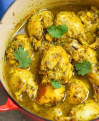 Trinidad curry chicken in a pot garnished with cilantro