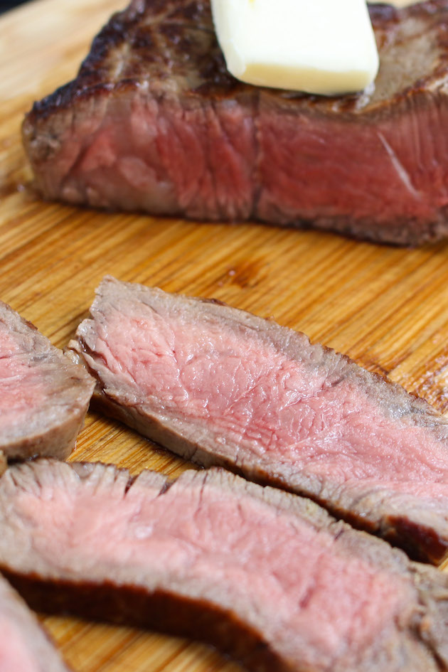 Pan-seared sirloin steak cooked to medium-rare and cut crosswise into thin slices on a wooden cutting board