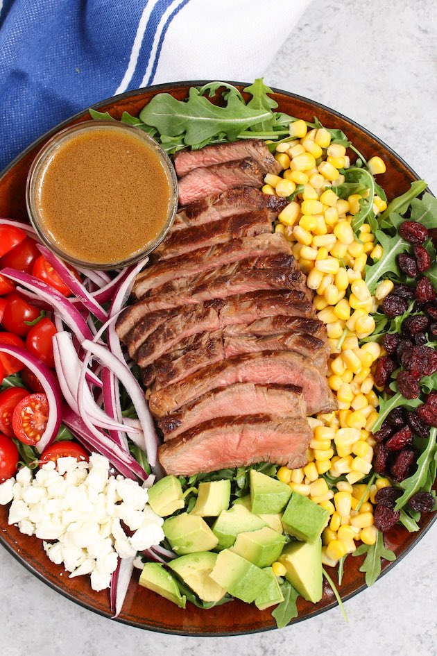 Steak salad severed on a large plate with balsamic vinaigrette dressing