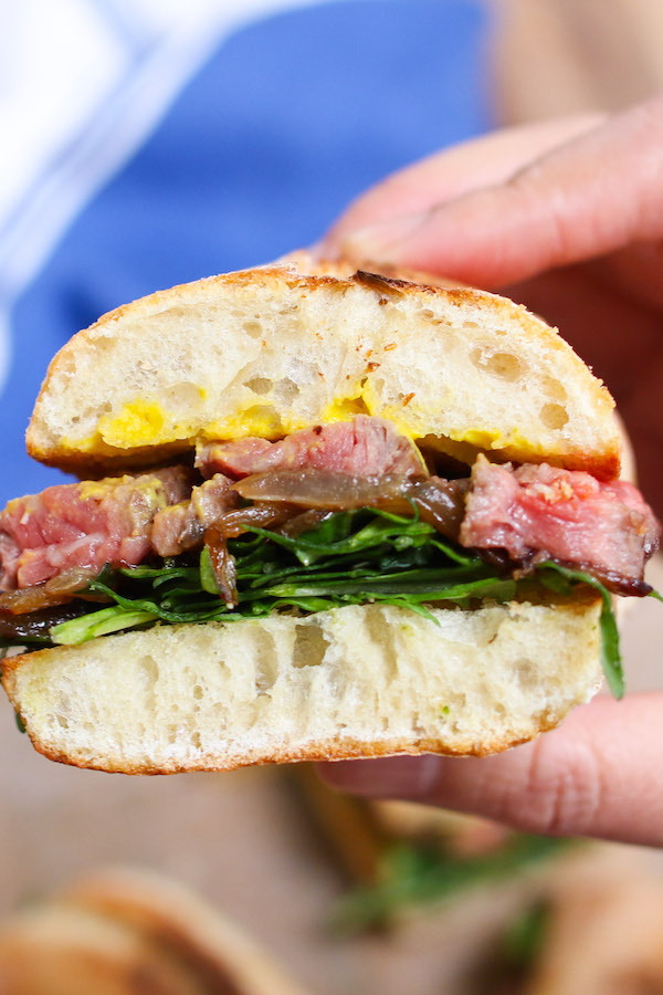 This steak sandwich recipe involves pan-seared steak, caramelized onions, arugula and mustard. There is a good mix of protein, vegetables and dressing piled between carbs.