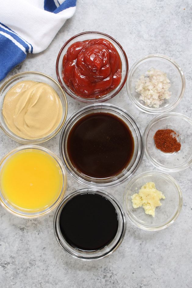 All ingredients displayed on the counter: ketchup, Dijon mustard, balsamic vinegar, orange juice, Worcestershire sauce, minced garlic, sliced shallot and cayenne pepper