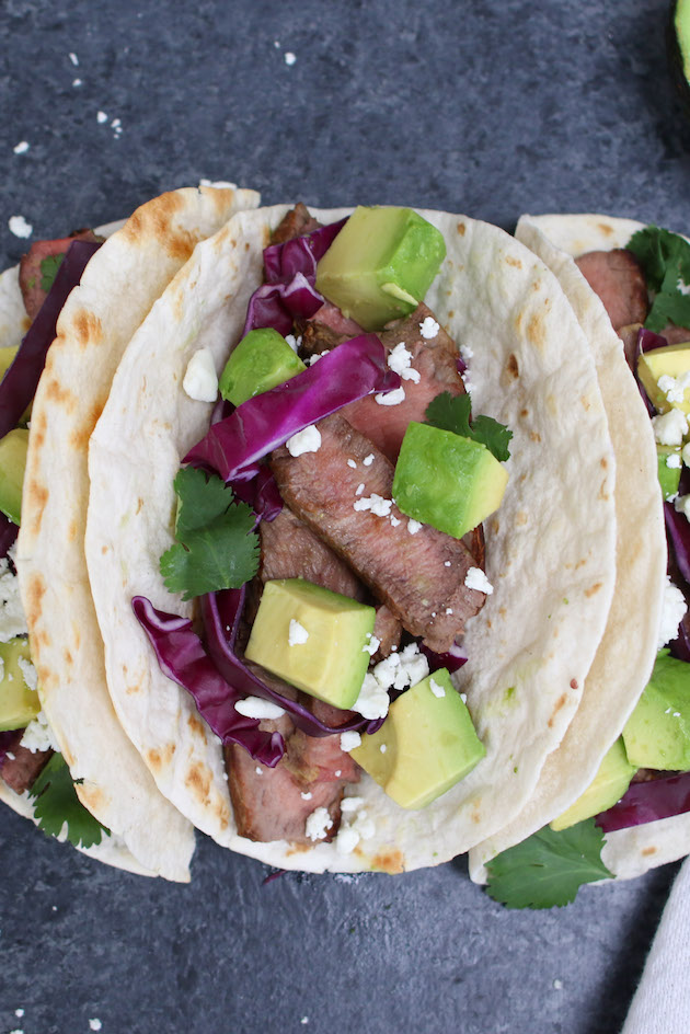 Homemade steak tacos made with sirloin steak, hot flour tortillas, toppings and queso fresco cheese for a delicious lunch or dinner idea