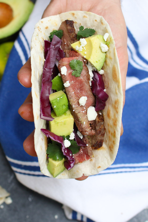 You can make steak tacos on the grill or stovetop - this photo shows a simple grilled steak taco held in the hand