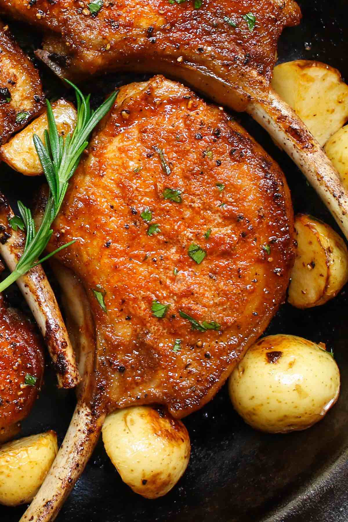 Closeup of stove top pork chops with a perfect golden crust and sauteed potatoes on the side
