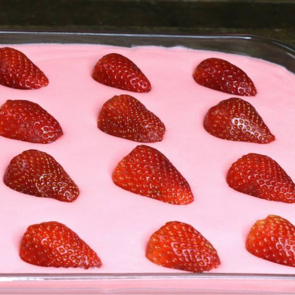 Here is a close-up photo of halved fresh strawberries floating beautifully on top of the filling in strawberry jello cake before the mirror glaze is added