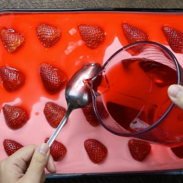 This is a photo showing how to pour the strawberry jello glaze onto the back of a spoon so it dribbles gently onto the filling layer in strawberry jello cake