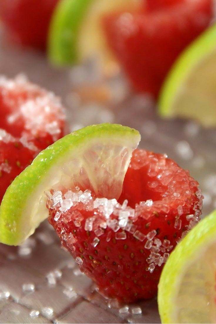 Here is a close-up view of a beautiful strawberry margarita jello shot served with a twist of lime on a plate