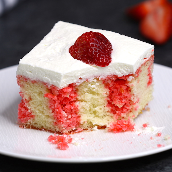 This photo shows a serving of strawberry poke cake that has been partially eaten and shows the beautiful contrast of red and white colors in the cake layer and crumbs on the plate