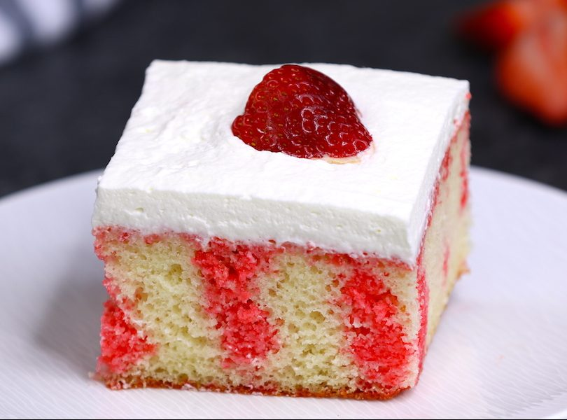 A piece of Strawberry Jello Poke Cake on a serving plate showing beautiful streaks of strawberry jello in the cake layer - it's a delicious dessert that's easy to make with a few simple ingredients