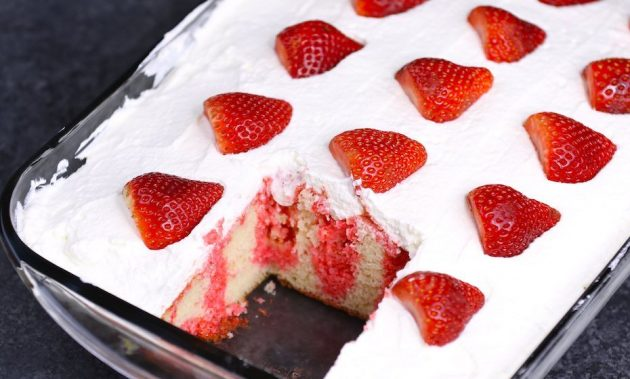 Strawberry Jello Poke Cake in the Pan after the first piece has been served, showing the arrangement of fresh strawberries on top along with the smooth cream layer and strawberry jello permeating into the poke holes in the cake